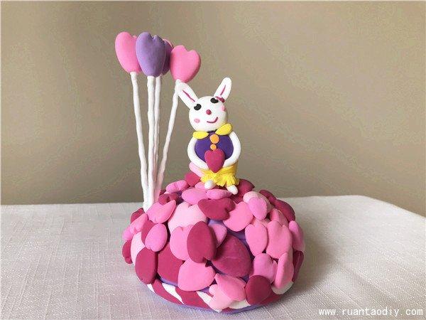 可爱的小白兔仰望着天空,背后还有几个气球,这款粘土作品看上去还有一